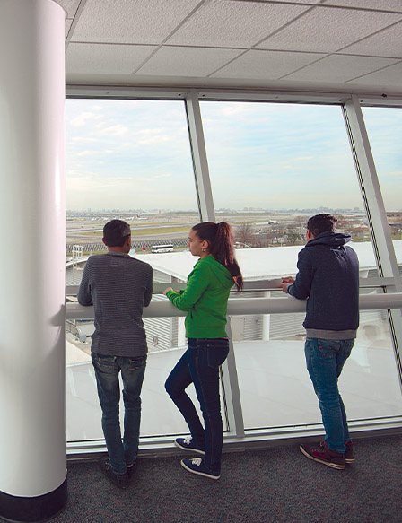 Students looking through a window at an air field