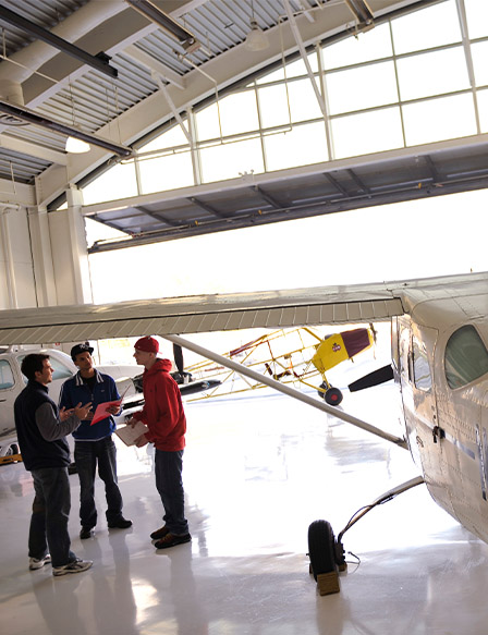3 students talking by plane in hangar