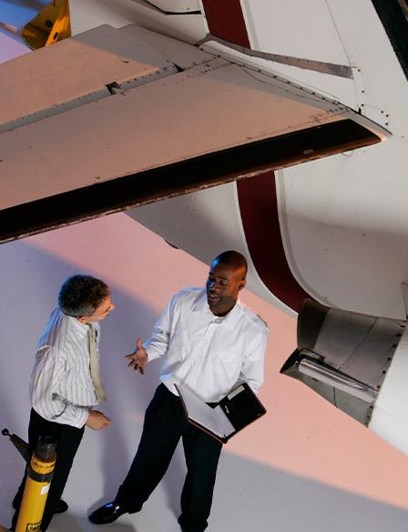 Two men talking in airplane hangar