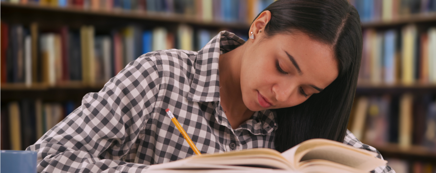 Latina girl studying for final exam in library
