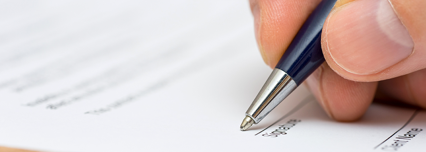 person-holding-pen-and-signing-document