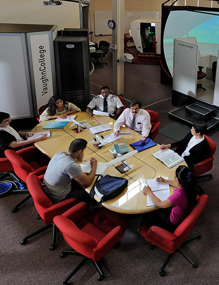 Students and faculty meeting at a table